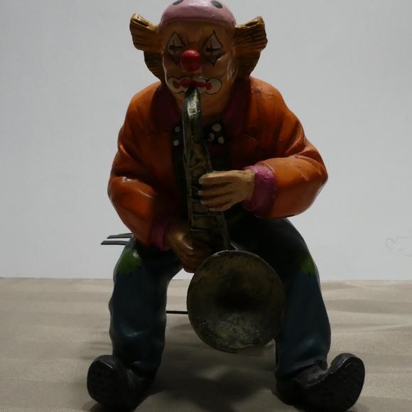 CLOWN porcelain sitting on bench playing saxophone